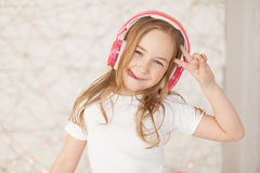 Music and technology. Young girl with pink wireless headphones make peace by hand and show tongue on background with Stock Photos