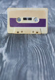 Music template postcard. Violet audio cassette on the gray wooden background. Stock Photo