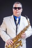 Music Themes. Portrait Of Confident Mature Male Saxophonist. Posing with Instrument in White Suit and Sunglasses. Against Black Background.Vertical Image Stock Images