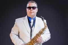 Music Themes. Portrait Of Confident Mature Male Saxophonist Posi. Ng with Instrument in White Suit and Sunglasses. Against Black Background.Horizontal Image Stock Photography