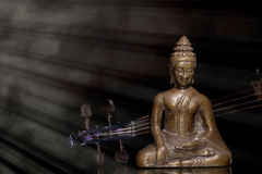 Music therapy. Spiritual, New Age, and religious music. Bronze buddha meditatin. G with comtemporary violin in divine beam of light. Traditional classical music Royalty Free Stock Photo