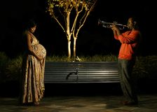 Music To Her Belly. African american couple in outdoor park at night. the husband playing trumpet for his wife and the baby in belly. great concept shot. there stock image