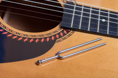 Music tuning fork on acoustic guitar strings. Music tuning fork on acoustic guitar metal strings Stock Images