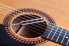 Music tuning fork on acoustic guitar strings Royalty Free Stock Image