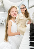 Music tutor teaches little girl to play piano Royalty Free Stock Photography