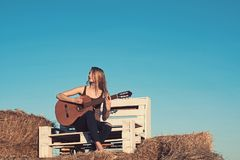 Music woman play guitar on wooden bench on blue sky. Music, woman guitarist perform concert on acoustic guitar. Music woman play guitar on wooden bench on blue stock photos