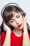 Music woman. Woman in red listening to music over big headphones, holding it Stock Image
