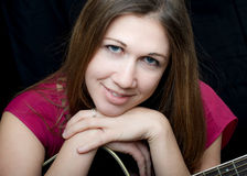 Music Woman. A smiling woman sits in front of a black background and plays guitar in a pink dress Stock Photos