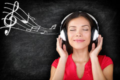 Music - woman wearing headphones listening to music. With music notes drawn on black blackboard texture background. Serene relaxing beautiful young multiracial Royalty Free Stock Photos