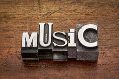 Music word in metal type. Music word in mixed vintage metal type printing blocks over grunge wood stock photography