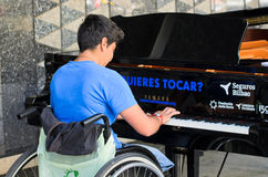 Music in your hands. BILBAO, SPAIN - APRIL 4, 2014: A woman in a Wheelchair plays a grand piano during music initiative BILBAO SE LLENA DE PIANOS consisting of Stock Images