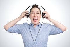 Musica aggressiva d'ascolto della ragazza emozionale del ritratto in cuffie Fotografia Stock
