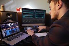 Musica componente del giovane sul computer portatile in camera da letto Fotografie Stock Libere da Diritti