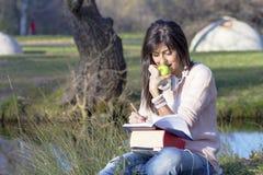 Musica d'apprendimento e d'ascolto della giovane donna in un parco di autunno Fotografie Stock Libere da Diritti