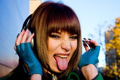 Musica d'ascolto allegra della giovane donna in cuffie Fotografie Stock