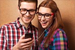 Musica d'ascolto dei pantaloni a vita bassa insieme Immagini Stock