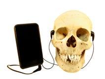 Musica d'ascolto del cranio umano con le cuffie su un telefono cellulare Fotografie Stock