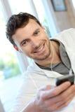 Musica d'ascolto del giovane con il telefono Fotografie Stock Libere da Diritti