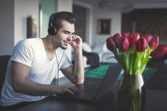 Musica d'ascolto del giovane dal computer portatile a casa Fotografia Stock Libera da Diritti