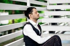 Musica d'ascolto del giovane uomo attraente I pantaloni a vita bassa bei meditano Fotografia Stock
