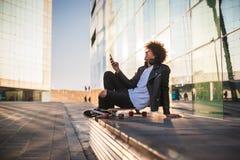 Musica d'ascolto del giovane uomo di colore con il cellulare e le cuffie in città soleggiata fotografie stock libere da diritti