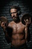 Musica d'ascolto del giovane uomo estetico atletico Fotografia Stock