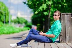 Musica d'ascolto del ragazzo dallo smartphone sulle vacanze estive Giovane turista attraente con il telefono cellulare all'aperto Fotografie Stock Libere da Diritti