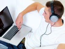 Musica d'ascolto del tirante in cuffia dal computer portatile Fotografie Stock Libere da Diritti