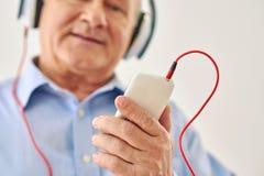 Musica d'ascolto dell'uomo anziano che tiene il telefono fotografia stock libera da diritti