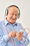 Musica d'ascolto dell'uomo anziano sulle cuffie fotografie stock