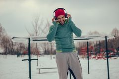 Musica d'ascolto dell'uomo atletico nel suo allenamento il giorno di inverno fotografia stock