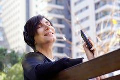 Musica d'ascolto dell'uomo con il suo smartphone fotografia stock