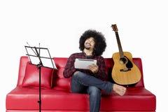 Musica d'ascolto dell'uomo di afro con il trasduttore auricolare Fotografie Stock Libere da Diritti