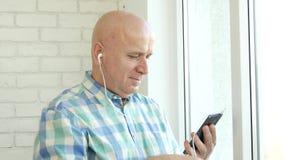 Musica d'ascolto dell'uomo felice in cuffie facendo uso della lista musicale radiofonica del cellulare video d archivio