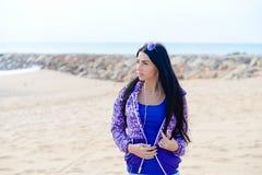 Musica d'ascolto della bella donna sportiva sulla spiaggia Fotografia Stock