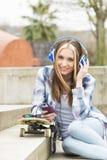 Musica d'ascolto della bella ragazza allegra dei pantaloni a vita bassa nella via Immagini Stock Libere da Diritti