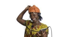 Musica d'ascolto della donna africana con il PC della compressa Immagini Stock