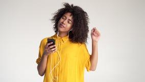 Musica d'ascolto della donna afroamericana facendo uso delle cuffie del telefono cellulare video d archivio