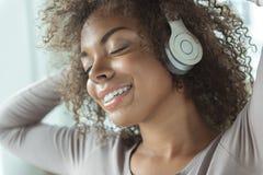 Musica d'ascolto della donna allegra a casa Immagine Stock