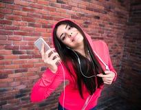 Musica d'ascolto della donna allegra felice sopra il muro di mattoni Immagine Stock