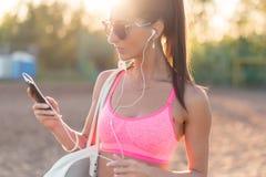 Musica d'ascolto della donna dell'atleta che esamina smartphone dopo l'allenamento nella sera di estate del ritratto della natura Fotografia Stock