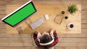 Musica d'ascolto della donna di affari rilassata in cuffie alla pausa di lavoro Esposizione verde del modello dello schermo archivi video