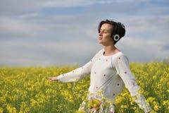Musica d'ascolto della donna emozionale e felice in cuffie i Fotografie Stock