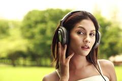 Musica d'ascolto della donna esterna Immagini Stock Libere da Diritti