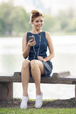 Musica d'ascolto della donna felice sulla linea con le cuffie Fotografie Stock Libere da Diritti