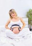 Musica d'ascolto della donna incinta in cuffie fotografia stock libera da diritti