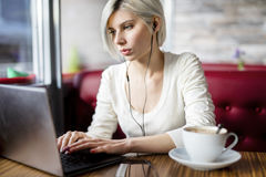 Musica d'ascolto della donna mentre lavorando al computer portatile in caffè Fotografie Stock
