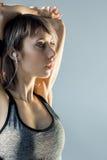 Musica d'ascolto della donna sportiva in cuffie mentre allungando Fotografie Stock