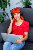 Musica d'ascolto della donna della testarossa con un computer portatile Immagini Stock