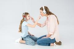 Musica d'ascolto della figlia e della madre con le cuffie in studio fotografia stock